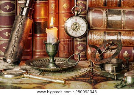 Vintage concept of discoveries: traveler accessories (antique spyglass, magnifier, sundial, compass), pocket watch and burning candle in an old candlestick are on the background of antique books poster