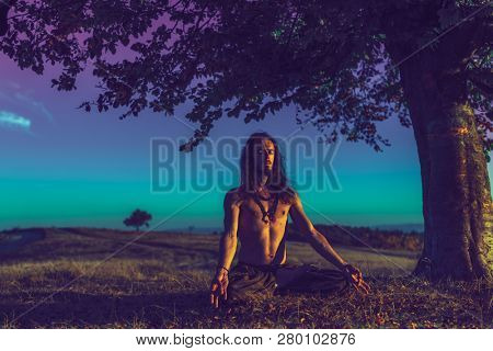 Yogi man meditating at sunset on the hills. Lifestyle emotional relaxation emotional concept spirituality harmony with nature