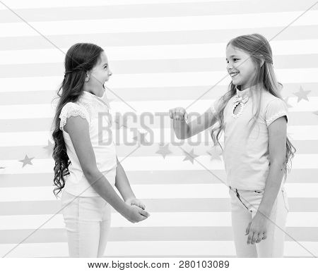 Kids schoolgirls preteens happy play together. Girls smiling happy faces play game communicating stand striped background. Girls children best friends involved communication game. Communicating skill. poster