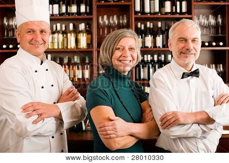 Restaurant manager posing with chef cook and waiter wine bar
