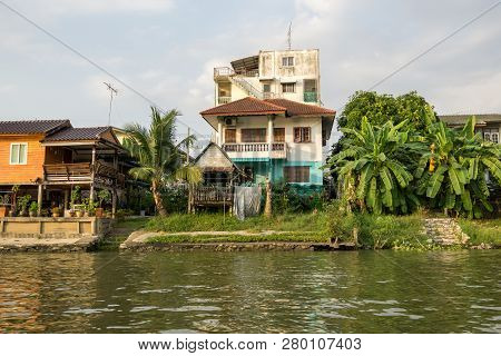 Chao Phraya Houses And Boats On The Riverside During Sunset Hours Taken From The Boat Ride. Ayutthay