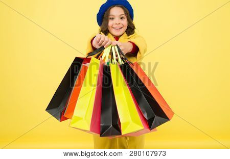 Fashionista Adore Shopping. Obsessed With Shopping. Girl Cute Kid Hold Shopping Bags On Yellow Backg
