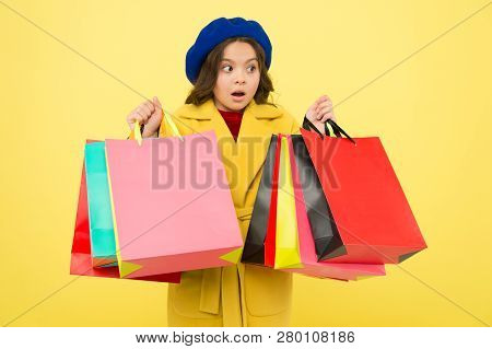 Obsessed With Shopping. Girl Cute Kid Hold Shopping Bags On Yellow Background. Mid Season Sale. Shop