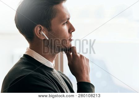 Pensive Young Handsome Man Have A Call With A Colleague And Looking Through The Window In Office, Ta