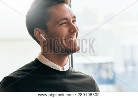 Portrait Of Happy Young Handsome Man Speaking With A Friend Telling Good News Using Wireless Earphon