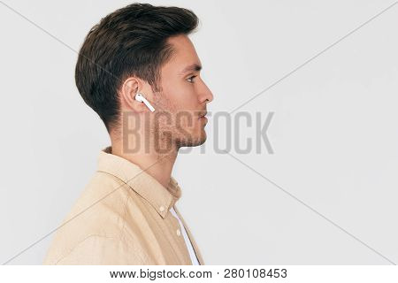 Side View Portrait Of Serious Young Handsome Man Posing With Wireless Earphones On White Studio Back