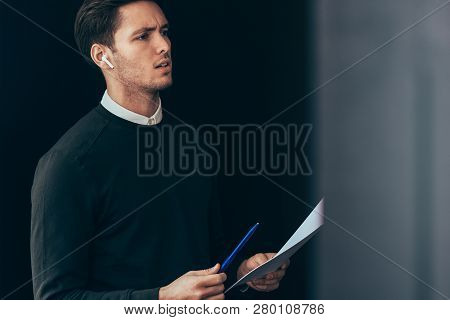 Serious Young Handsome Man Have A Conversation With Colleagues During Meeting With Wireless Earphone