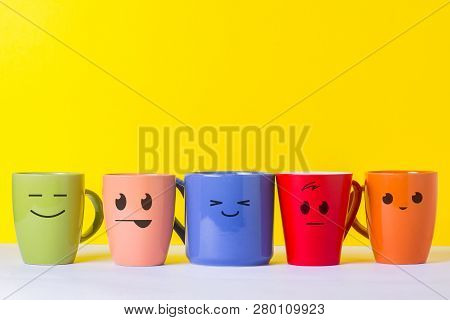 A Lot Of Multi-colored Cups With Funny Faces On A Yellow Background. The Concept Of A Friendly Compa
