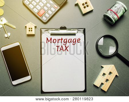 Table With Wooden Houses, Calculator, Coins, Magnifying Glass With The Word Mortgage Tax. Property T
