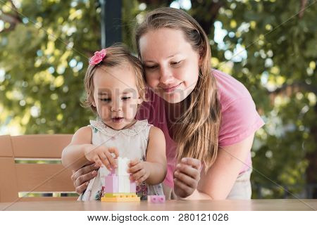 Happy Smiling Mother And Baby Daughter Having Fun And Playing With Toys Outdoors In Summer