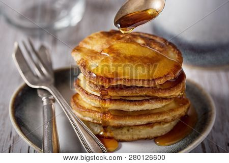 Shrove Tuesday, Pancake Day.  Pancakes Poured With Honey On The Background Of Vintage Plates, Forks