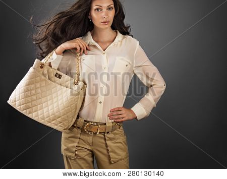 Elegant woman in silk  blouse  and beige trousers holding leather bag.