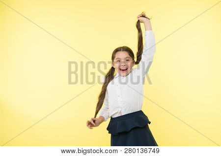 Comfortable and easy hairstyle. Deal with long hair hairstyle by yourself. Kid girl long ponytail hairstyle. Child school uniform make hairdo. Kid stylish fashionable posing hold ponytails hairstyle. poster