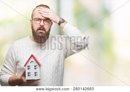 Young caucasian real state agent man holding house isolated background stressed with hand on head, shocked with shame and surprise face, angry and frustrated. Fear and upset for mistake.