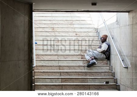 Lisbon, Portugal, 30 September, 2018: Dirty Homeless Person Sitting On Stairs