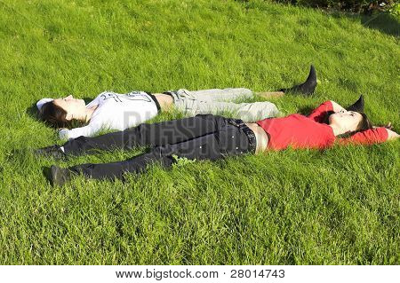 two young beauty girls lying on green grass
