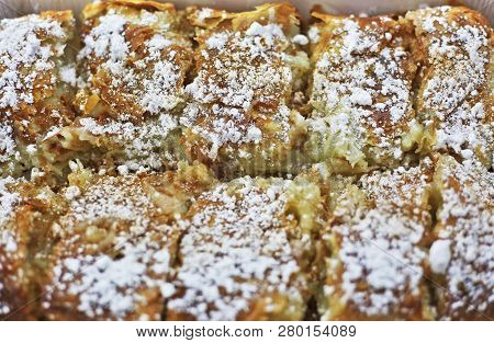 Close Up Of The Traditional Greek Bougatsa - Phyllo Pastry Filled With Cream And Garnished With Powd
