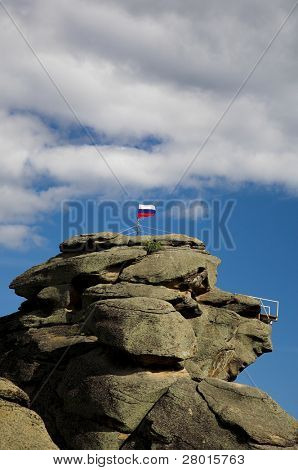 Russian flag on the rock against cloudy sky