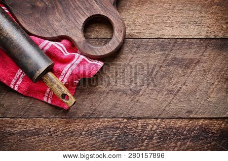 Wooden Walnut Cutting Board And Vintage Rolling Pin Over Red Kitchen Towel And Rustic Old Barn Wood