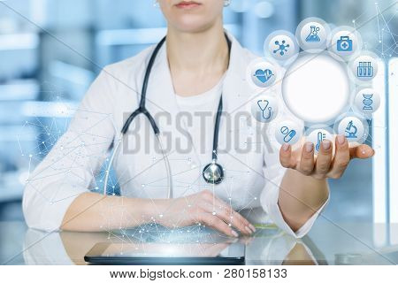 A Closeup Of Doctor With Stethoscope Sitting At A Table With A Digital Device On It And Holding A Ci