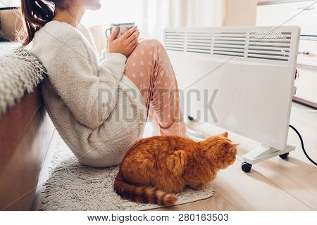 Using Heater At Home In Winter. Woman Warming And Drinking Tea With Cat. Heating Season.