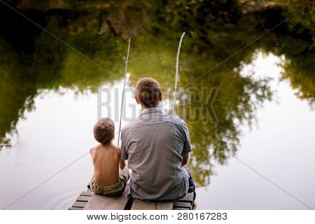 Dad And Son Fishing Outdoors, View From Back. Father And His Son Fishing Together From Wooden Jetty