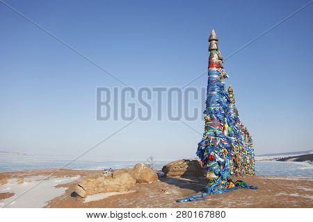 Wooden Ritual Pillars With Multicolored Ribbons On Cape Burkhan Of Olkhon Island, Lake Baikal. Siber
