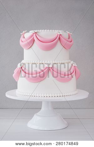 White Wedding Cake With Pink Elements Made From Pastry Mastic On A Wooden Background. Sugar Flowers,