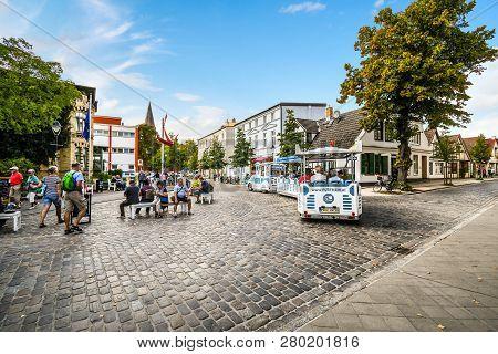 Warnemunde, Germany - September 4 2018: Tourists Ride A Blue Bus Fun Tour Tram Through The Streets O