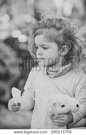 Child With Long Blond Hair Hold Comb And Toy Horse On Natural Background. Girl Beauty, Look, Hairsty