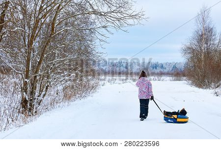 A Young Mother Rolls A Small Child In The Winter In The Park. Russian Winter.