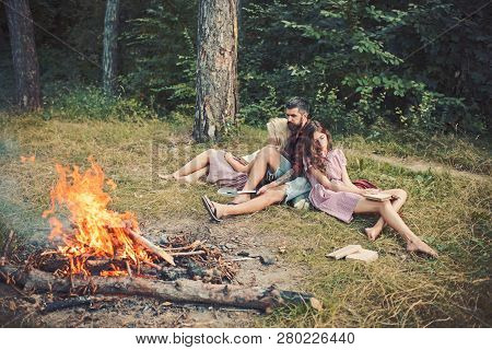 Friends Relax At Campfire. People At Bonfire Flame In Green Forest. Women And Man At Fire In Camp. C