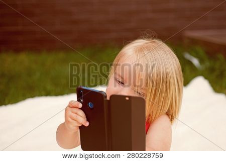 Cell Phone Dependency. Small Child Make Phone Call. Small Girl Use Mobile Phone. Girl Child With Blo