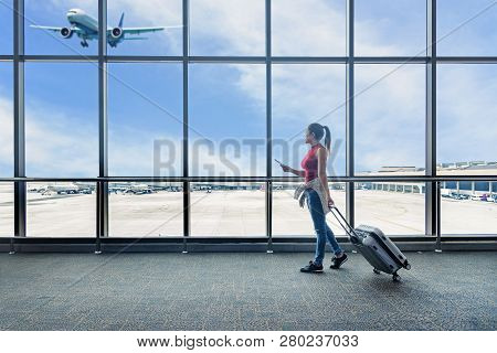 Traveler Women Plan And Backpack See The Airplane At The Airport Glass Window. Asian Tourist Hold Ba