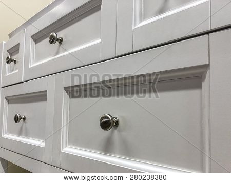Wood kitchen cabinets. Modern base cabinets with chrome cabinet handles. Modern Cabinets. Contemporary Italian kitchen cabinet design. Base doors and drawers of wooden kitchen cabinet.