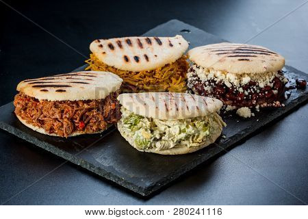 Venezuelan Latin American Food, 4 Arepas Of Different Stuffing On A Black Table. Arepa With Mechada