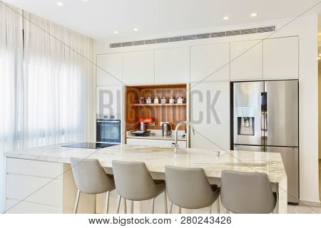 Modern Design Of Luxury White Kitchen With Marble Island And Dinner Table