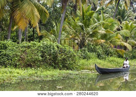 Backwaters, India - August 24: Man In Canoe On August 24, 2011 In Backwaters, India. The Kerala Back