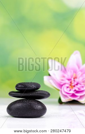 Balanced Zen Stones With Drops Of Water And Waterlily On A Green Bokeh Background