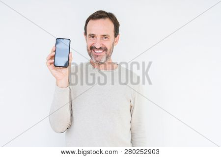 Senior man showing smartphone screen over isolated background with a happy face standing and smiling with a confident smile showing teeth