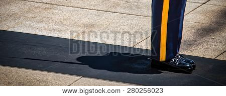 The Shadow Of A Us Army Soldier Standing At Attention, With His Rifle, On Guard Duty.