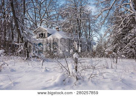 Old Abandoned White Wooden House Among Snow-covered Trees On A Frosty Winter Day.