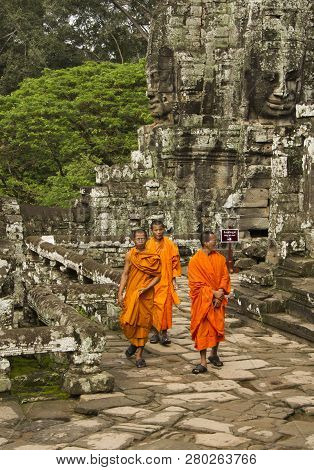 Siem Riep, Cambodia - Oct 9, 2011: Three Monks Walking Among Ancient Temple Ruins