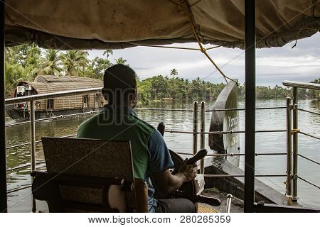 Alleppey, India, Mar 13, 2018: Man Drives A Houseboat Through The Backwaters Of Kerala