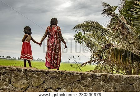 Alleppey, India, Mar 13, 2018: Mother And Daughter Stand On Bank Of Canal Holding Hands