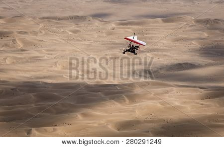Walvis Bay, Namibia - July 16, 2018: An Ultralight Aircraft Is Seen Flying With Sand Dunes As A Back