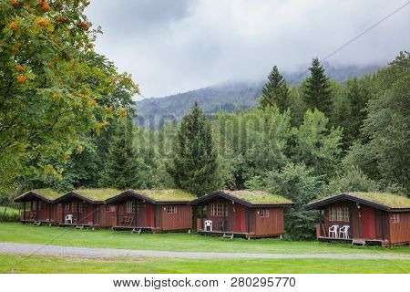Wooden cabins with sod or turf roof at a campsite in Norway Scandinavia