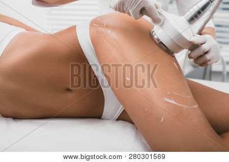 woman having cavitation procedure, cellulite treatment, on her buttocks and legs poster