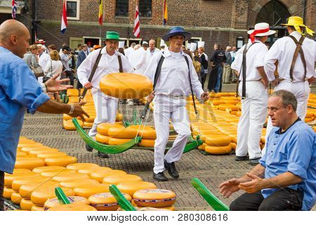 Alkmaar, The Netherlands - September 7: Carriers Walking With Many Cheeses In The Famous Dutch Chees