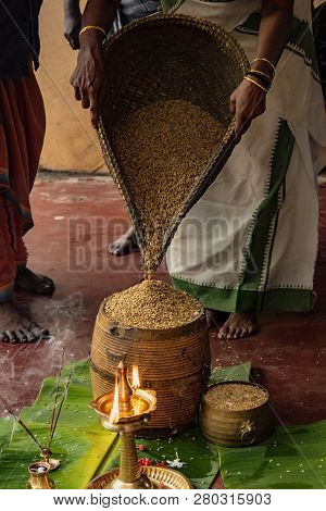 Alleppey, India, Mar 13, 2018: Woman Pours Grain Into Basket As Offering To The Hindu Temple